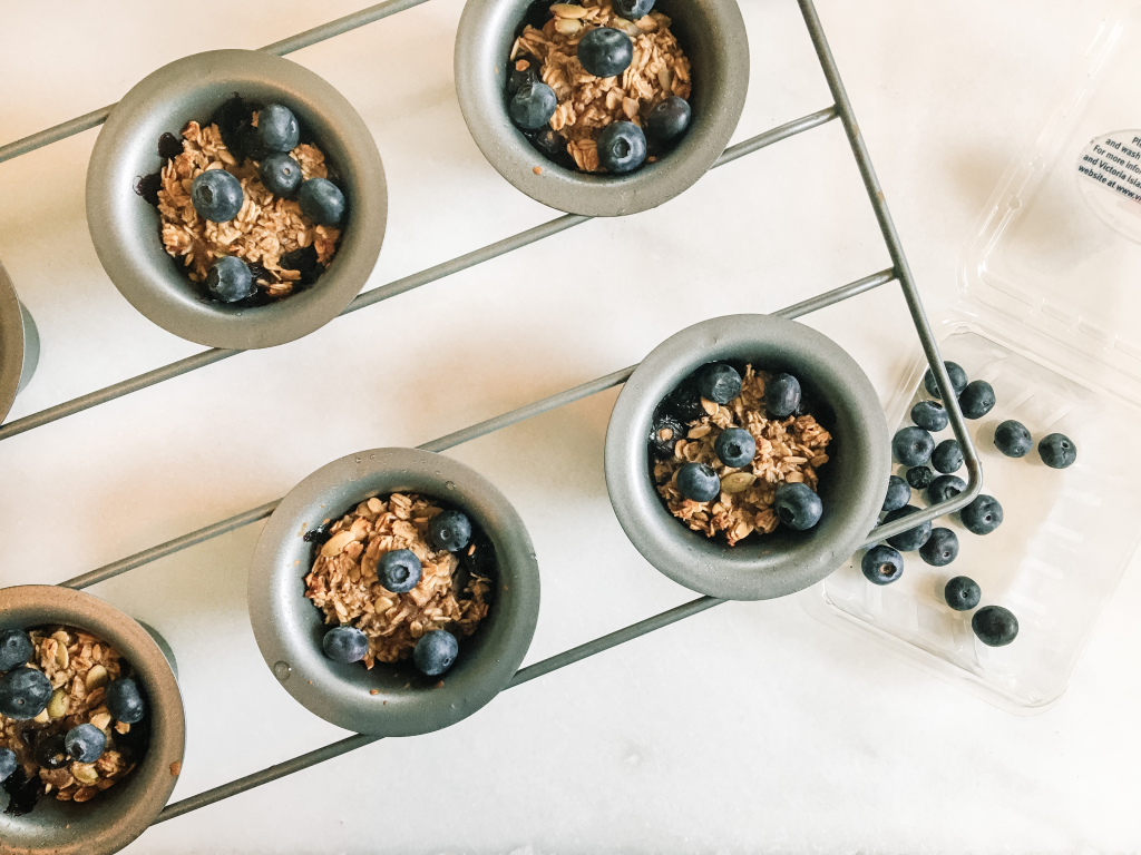 Blueberry baked oatmeal cups in pan with blueberry conatiner
