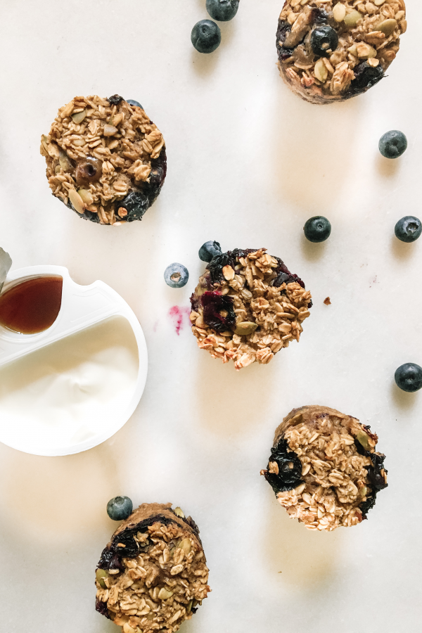 Blueberry baked oatmeal cups on marble with container of yogurt