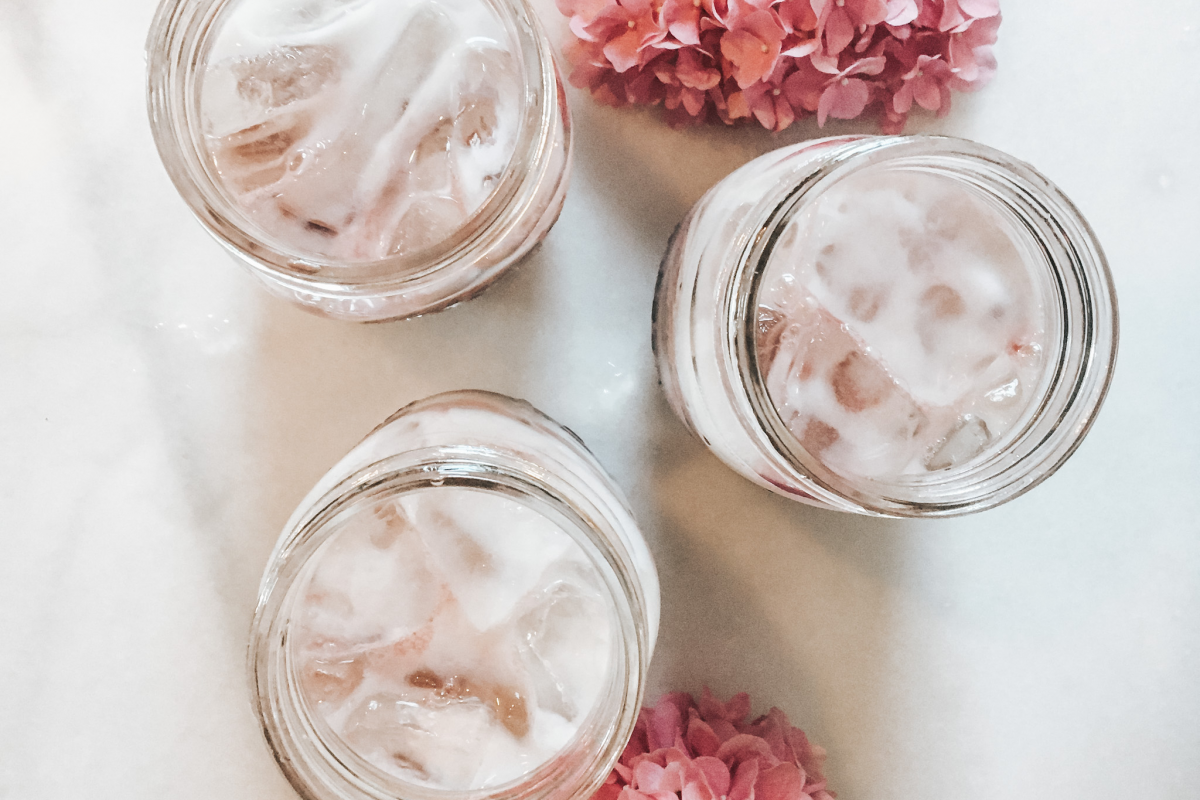 Hibiscus iced latte in three mason jars with flowers