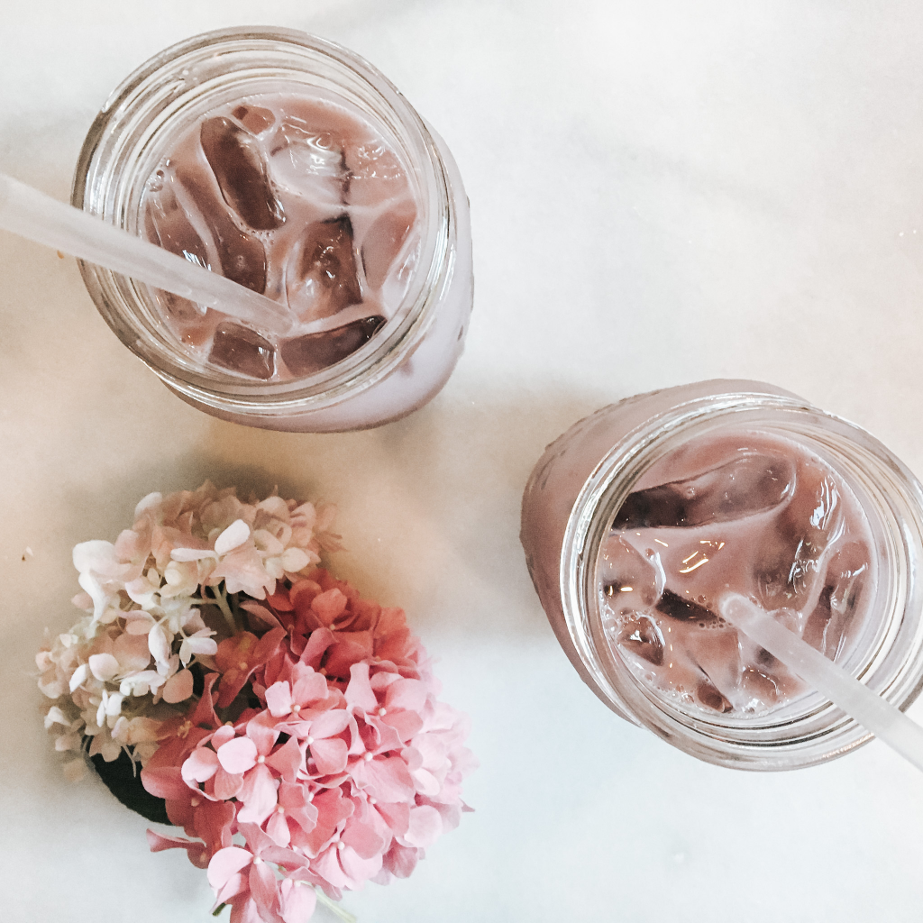 Hibiscus iced latte in mason jar with straw and flowers