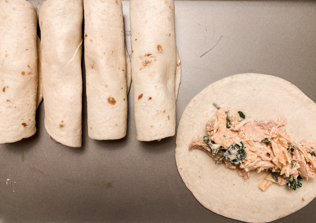 Creamy chicken and spinach taquito on tray rolled